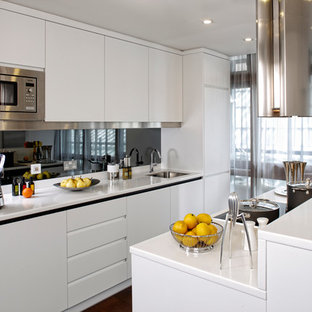 Photo of a contemporary galley enclosed kitchen in London with a submerged sink, flat-panel cabinets, white cabinets, metallic splashback, stainless steel appliances and an island.