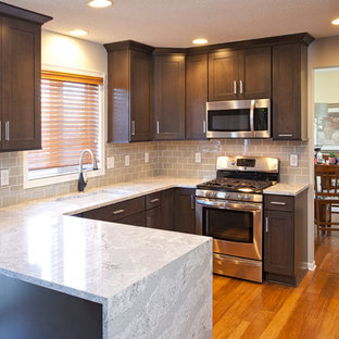 Mid-sized transitional eat-in kitchen photos - Mid-sized transitional u-shaped medium tone wood floor eat-in kitchen photo in Minneapolis with an undermount sink, flat-panel cabinets, dark wood cabinets, gray backsplash, glass tile backsplash, stainless steel appliances and a peninsula