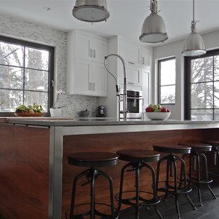 カルガリーの大きいインダストリアルスタイルのおしゃれなキッチン (シェーカースタイル扉のキャビネット、白いキャビネット、ステンレスカウンター、グレーのキッチンパネル、モザイクタイルのキッチンパネル、シルバーの調理設備の、スレートの床) の写真