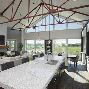 カルガリーの大きいインダストリアルスタイルのおしゃれなキッチン (アンダーカウンターシンク、シェーカースタイル扉のキャビネット、白いキャビネット、マルチカラーのキッチンパネル、ボーダータイルのキッチンパネル、シルバーの調理設備の、無垢フローリング、茶色い床) の写真