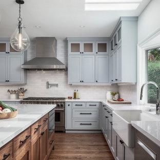 サンフランシスコの広いトランジショナルスタイルのおしゃれなキッチン (エプロンフロントシンク、シェーカースタイル扉のキャビネット、クオーツストーンカウンター、白いキッチンパネル、レンガのキッチンパネル、シルバーの調理設備、無垢フローリング、茶色い床、白いキッチンカウンター、グレーのキャビネット) の写真