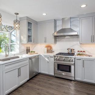Mittelgroße Klassische Küche ohne Insel in U-Form mit Quarzwerkstein-Arbeitsplatte, Küchenrückwand in Weiß, Küchengeräten aus Edelstahl, braunem Holzboden, braunem Boden, weißer Arbeitsplatte, Doppelwaschbecken, Schrankfronten im Shaker-Stil und grauen Schränken in San Francisco