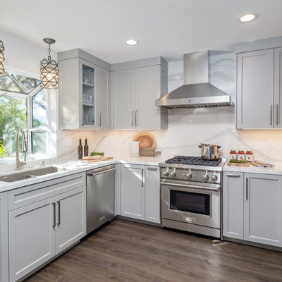 Example of a mid-sized transitional u-shaped medium tone wood floor and brown floor kitchen design in San Francisco with quartz countertops, white backsplash, stainless steel appliances, no island, white countertops, a double-bowl sink, shaker cabinets and gray cabinets