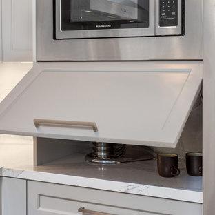 サンフランシスコの中サイズのモダンスタイルのおしゃれなダイニングキッチン (アンダーカウンターシンク、白いキャビネット、クオーツストーンカウンター、白いキッチンパネル、ガラスタイルのキッチンパネル、シルバーの調理設備の、無垢フローリング、アイランドなし、茶色い床、白いキッチンカウンター) の写真