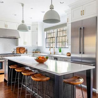 シカゴの中くらいのビーチスタイルのおしゃれなキッチン (アンダーカウンターシンク、シェーカースタイル扉のキャビネット、白いキャビネット、クオーツストーンカウンター、白いキッチンパネル、シルバーの調理設備、無垢フローリング、白いキッチンカウンター、サブウェイタイルのキッチンパネル) の写真