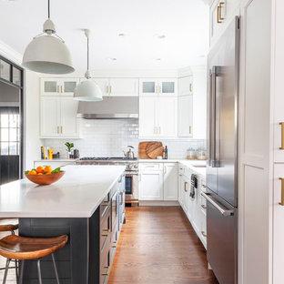 Mittelgroße Maritime Wohnküche in L-Form mit Unterbauwaschbecken, Schrankfronten im Shaker-Stil, weißen Schränken, Quarzwerkstein-Arbeitsplatte, Küchenrückwand in Weiß, Rückwand aus Keramikfliesen, Küchengeräten aus Edelstahl, braunem Holzboden, Kücheninsel, braunem Boden und weißer Arbeitsplatte in Chicago