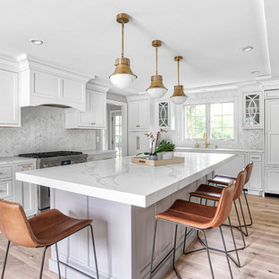 Large transitional eat-in kitchen designs - Inspiration for a large transitional u-shaped light wood floor and beige floor eat-in kitchen remodel in New York with paneled appliances, an island, an undermount sink, beaded inset cabinets, white cabinets, quartz countertops, white backsplash, mosaic tile backsplash and white countertops