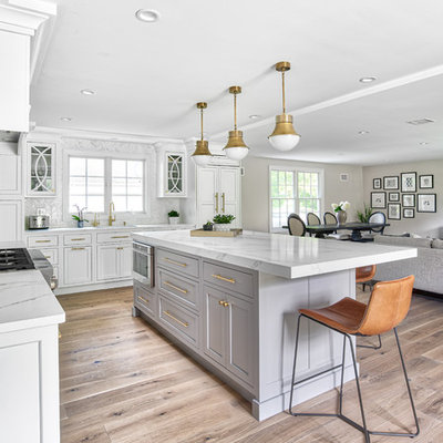 Open concept kitchen - large transitional l-shaped open concept kitchen idea in New York with an undermount sink, beaded inset cabinets, white cabinets, quartz countertops, white backsplash, mosaic tile backsplash, paneled appliances, an island and white countertops