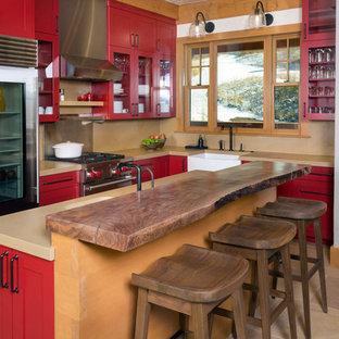 Urige Küche mit Landhausspüle, Glasfronten, roten Schränken, Küchenrückwand in Beige, Küchengeräten aus Edelstahl und Kücheninsel in Denver