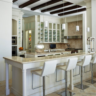 This is an example of a traditional kitchen in Miami with glass-front cabinets, beige cabinets, beige splashback, stainless steel appliances and with island.