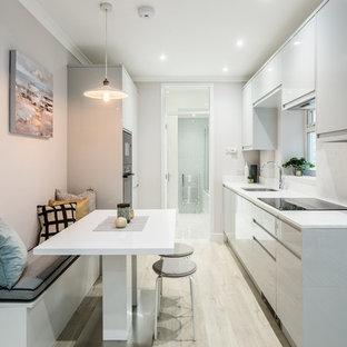 Imagen de cocina de galera, contemporánea, pequeña, abierta, con fregadero encastrado, armarios con paneles lisos, puertas de armario grises, encimera de acrílico, electrodomésticos con paneles, suelo laminado, suelo beige y encimeras blancas