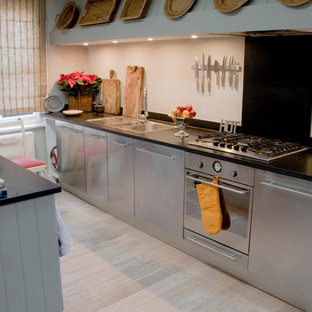 This is an example of a small modern galley separate kitchen in London with flat-panel cabinets, stainless steel cabinets, marble benchtops, black splashback, ceramic splashback, light hardwood floors and no island.