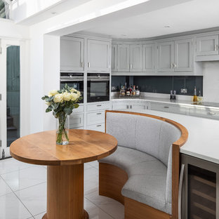 Design ideas for a traditional l-shaped kitchen/diner in London with shaker cabinets, grey cabinets, glass sheet splashback, an island, white floors and white worktops.