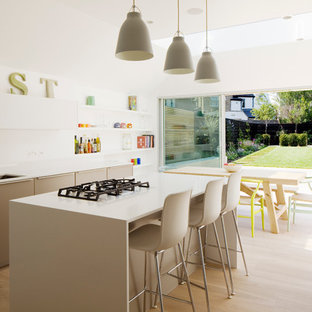 Mid-sized contemporary eat-in kitchen ideas - Inspiration for a mid-sized contemporary l-shaped light wood floor and beige floor eat-in kitchen remodel in London with flat-panel cabinets, solid surface countertops, white backsplash, an island, an undermount sink, beige cabinets, glass sheet backsplash, stainless steel appliances and beige countertops
