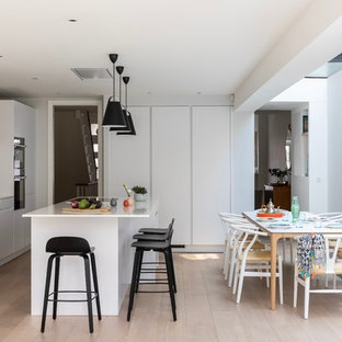 Design ideas for a large contemporary galley kitchen/diner in London with an integrated sink, flat-panel cabinets, white cabinets, limestone worktops, white splashback, limestone splashback, black appliances, light hardwood flooring, an island, beige floors and white worktops.