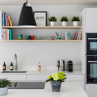Moderne Wohnküche mit flächenbündigen Schrankfronten, weißen Schränken, Kalkstein-Arbeitsplatte, Küchenrückwand in Weiß, Kalk-Rückwand, schwarzen Elektrogeräten, Kücheninsel, weißer Arbeitsplatte und Unterbauwaschbecken in London