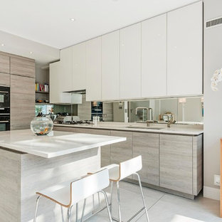 Photo of a medium sized modern l-shaped kitchen in London with a submerged sink, flat-panel cabinets, grey cabinets, metallic splashback, mirror splashback, integrated appliances, an island and grey floors.