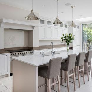 Mittelgroße, Zweizeilige Klassische Wohnküche mit Doppelwaschbecken, Glasrückwand, Küchengeräten aus Edelstahl, Kücheninsel, weißem Boden, weißer Arbeitsplatte, Schrankfronten im Shaker-Stil und weißen Schränken in London