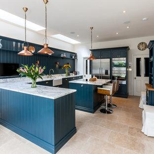 他の地域のカントリー風おしゃれなキッチン (エプロンフロントシンク、落し込みパネル扉のキャビネット、青いキャビネット、御影石カウンター、青いキッチンパネル、木材のキッチンパネル、シルバーの調理設備の、トラバーチンの床、ベージュの床) の写真