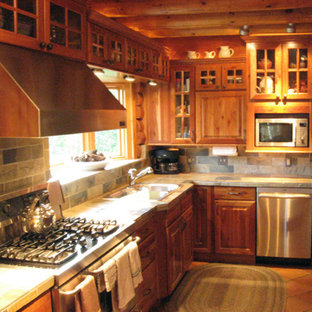 Photo of a mid-sized country l-shaped separate kitchen in Austin with a double-bowl sink, raised-panel cabinets, dark wood cabinets, tile benchtops, multi-coloured splashback, slate splashback, stainless steel appliances, terra-cotta floors, no island, orange floor and multi-coloured benchtop.