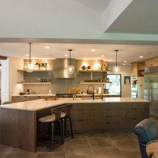 ミルウォーキーの中サイズのエクレクティックスタイルのおしゃれなキッチン (アンダーカウンターシンク、フラットパネル扉のキャビネット、中間色木目調キャビネット、珪岩カウンター、ベージュキッチンパネル、磁器タイルのキッチンパネル、シルバーの調理設備の、磁器タイルの床、黒い床、白いキッチンカウンター) の写真