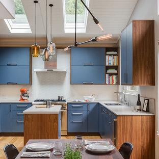 サンフランシスコの大きいモダンスタイルのおしゃれなキッチン (アンダーカウンターシンク、フラットパネル扉のキャビネット、青いキャビネット、人工大理石カウンター、白いキッチンパネル、石スラブのキッチンパネル、シルバーの調理設備の、淡色無垢フローリング、茶色い床) の写真