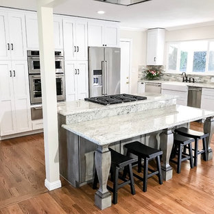 Mid-sized traditional eat-in kitchen remodeling - Mid-sized elegant l-shaped light wood floor and brown floor eat-in kitchen photo in Sacramento with a farmhouse sink, shaker cabinets, white cabinets, granite countertops, green backsplash, stone tile backsplash, stainless steel appliances and an island