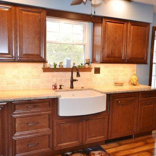 Inredning av ett klassiskt mellanstort beige beige kök, med en rustik diskho, luckor med upphöjd panel, skåp i mellenmörkt trä, granitbänkskiva, beige stänkskydd, stänkskydd i tunnelbanekakel, rostfria vitvaror, mellanmörkt trägolv och brunt golv
