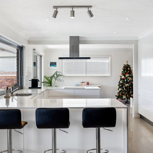 Photo of a mid-sized contemporary u-shaped eat-in kitchen in Gold Coast - Tweed with flat-panel cabinets, white cabinets, quartz benchtops, white splashback, subway tile splashback, white benchtop, a double-bowl sink, stainless steel appliances, a peninsula and beige floor.