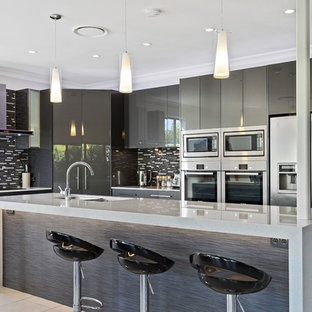 Photo of a mid-sized contemporary galley kitchen in Gold Coast - Tweed with flat-panel cabinets, grey cabinets, quartz benchtops, stainless steel appliances, ceramic floors, beige floor, an undermount sink, black splashback, matchstick tile splashback and an island.