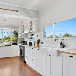 Inspiration for a transitional single-wall kitchen in Gold Coast - Tweed with a farmhouse sink, shaker cabinets, white cabinets, white splashback, black appliances and medium hardwood floors.