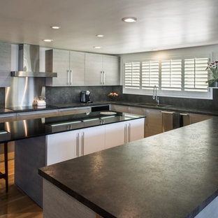 This is an example of a large contemporary u-shaped eat-in kitchen in Santa Barbara with stainless steel appliances, with island, an undermount sink, flat-panel cabinets, grey cabinets, onyx benchtops, black splashback, stone slab splashback and medium hardwood floors.