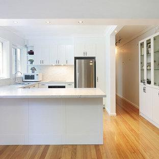 Foto på ett mellanstort vintage vit kök, med en nedsänkt diskho, skåp i shakerstil, vita skåp, bänkskiva i kvarts, vitt stänkskydd, stänkskydd i sten, rostfria vitvaror, plywoodgolv och gult golv