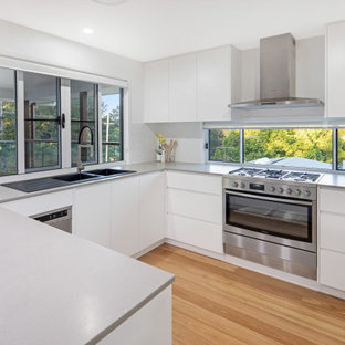 Photo of a mid-sized contemporary u-shaped kitchen in Sunshine Coast with a double-bowl sink, white cabinets, concrete benchtops, white splashback, subway tile splashback, stainless steel appliances, no island, flat-panel cabinets, medium hardwood floors, brown floor and grey benchtop.