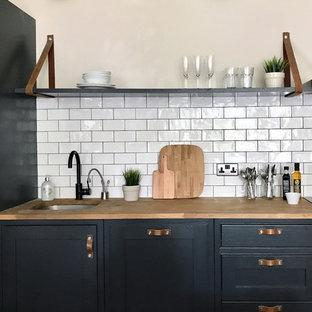 ロンドンの小さいエクレクティックスタイルのおしゃれなキッチン (シングルシンク、シェーカースタイル扉のキャビネット、黒いキャビネット、木材カウンター、白いキッチンパネル、セラミックタイルのキッチンパネル、シルバーの調理設備、無垢フローリング、アイランドなし) の写真