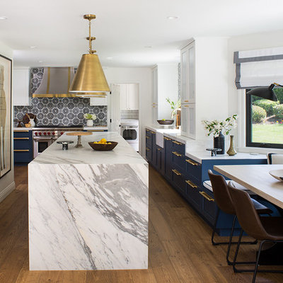 Example of a large transitional u-shaped medium tone wood floor and brown floor eat-in kitchen design in Los Angeles with a farmhouse sink, shaker cabinets, blue cabinets, multicolored backsplash, paneled appliances, an island, gray countertops, marble countertops and ceramic backsplash