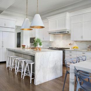 Esempio di una grande cucina chic con top in marmo, paraspruzzi bianco, paraspruzzi in lastra di pietra, ante con riquadro incassato, ante bianche, elettrodomestici da incasso, pavimento in legno massello medio, isola e lavello sottopiano