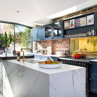 Photo of a medium sized farmhouse galley kitchen/diner in London with shaker cabinets, blue cabinets, engineered stone countertops, metallic splashback, metal splashback, black appliances, painted wood flooring, an island, white worktops and white floors.