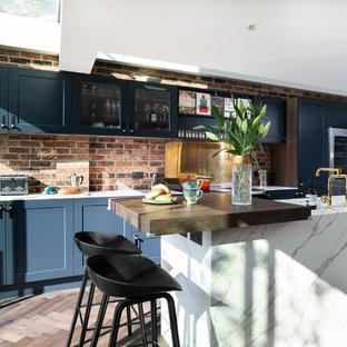 Design ideas for a mid-sized modern galley eat-in kitchen in Other with an integrated sink, shaker cabinets, blue cabinets, quartz benchtops, metallic splashback, metal splashback, black appliances, painted wood floors, with island, brown floor and white benchtop.