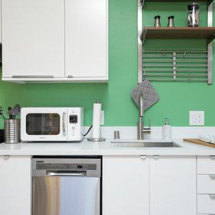 サンフランシスコの小さい北欧スタイルのおしゃれなキッチン (アンダーカウンターシンク、フラットパネル扉のキャビネット、白いキャビネット、クオーツストーンカウンター、白いキッチンパネル、クオーツストーンのキッチンパネル、シルバーの調理設備、ラミネートの床、アイランドなし、茶色い床、白いキッチンカウンター) の写真