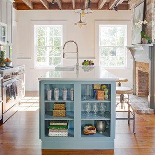 Неиссякаемый источник вдохновения для домашнего уюта: маленькая параллельная, отдельная кухня в стиле кантри с раковиной в стиле кантри, серыми фасадами, столешницей из кварцевого композита, синим фартуком, фартуком из терракотовой плитки, техникой из нержавеющей стали, паркетным полом среднего тона, островом, коричневым полом, белой столешницей и фасадами с утопленной филенкой