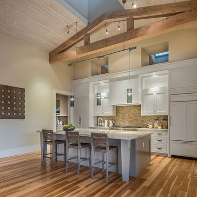 Kitchen - farmhouse galley medium tone wood floor and brown floor kitchen idea in San Francisco with an undermount sink, shaker cabinets, white cabinets, brown backsplash, paneled appliances and an island