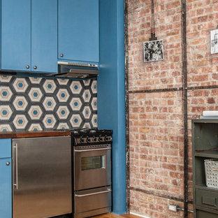 ニューヨークの小さいエクレクティックスタイルのおしゃれなキッチン (ドロップインシンク、フラットパネル扉のキャビネット、青いキャビネット、木材カウンター、マルチカラーのキッチンパネル、セメントタイルのキッチンパネル、シルバーの調理設備、無垢フローリング、アイランドなし) の写真