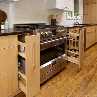 Inspiration for a small modern light wood floor and brown floor kitchen remodel in Seattle with a single-bowl sink, flat-panel cabinets, light wood cabinets, quartz countertops, white backsplash, ceramic backsplash and stainless steel appliances