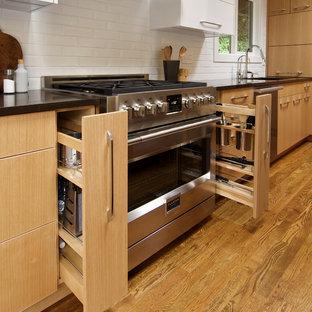 Geschlossene, Kleine Moderne Küche in L-Form mit Waschbecken, flächenbündigen Schrankfronten, hellen Holzschränken, Quarzwerkstein-Arbeitsplatte, Küchenrückwand in Weiß, Rückwand aus Keramikfliesen, Küchengeräten aus Edelstahl, hellem Holzboden, Kücheninsel und braunem Boden in Seattle