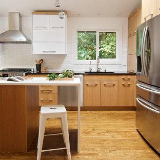 Bild på ett mellanstort funkis kök, med släta luckor, bänkskiva i kvarts, vitt stänkskydd, stänkskydd i keramik, rostfria vitvaror, en köksö, en undermonterad diskho, skåp i mellenmörkt trä, mellanmörkt trägolv och brunt golv