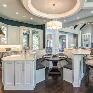 Inspiration for a large timeless single-wall dark wood floor and brown floor open concept kitchen remodel in Columbus with a farmhouse sink, flat-panel cabinets, white cabinets, white backsplash, paneled appliances and two islands
