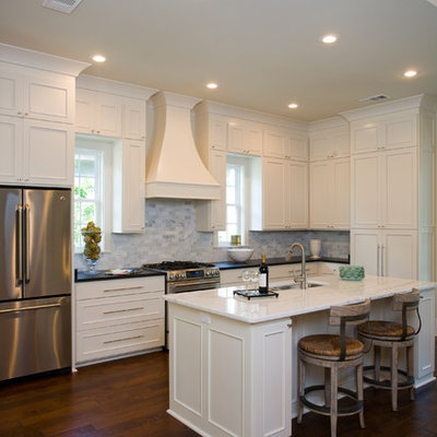 Example of a mid-sized classic galley enclosed kitchen design in New Orleans with recessed-panel cabinets, stainless steel appliances, stone tile backsplash, white cabinets, white backsplash and an island