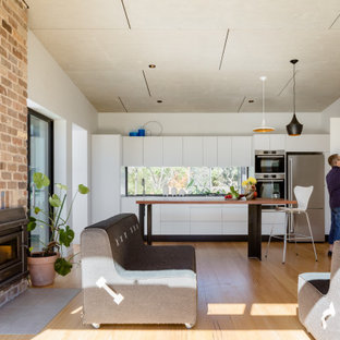 This is an example of a contemporary single-wall open plan kitchen in Sydney with flat-panel cabinets, white cabinets, window splashback, stainless steel appliances, medium hardwood floors, with island and brown floor.