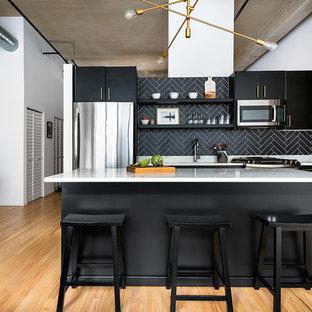 シカゴ, ILのインダストリアルスタイルのアイランドキッチンの写真 (フラットパネル扉のキャビネット、黒いキャビネット、黒いキッチンパネル、シルバーの調理設備の、淡色無垢フローリング、白いキッチンカウンター)